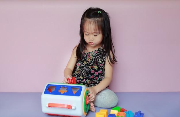 Menina asiática do miúdo que joga brinquedos plásticos coloridos