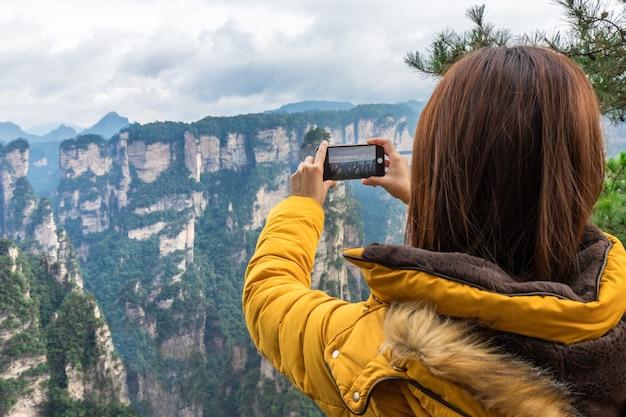 Menina asiática do turista que toma a foto usando o telefone esperto zhangjiajie wulingyuan changsha china