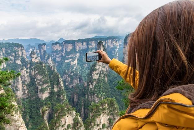Menina asiática do turista que toma uma foto zhangjiajie national park china
