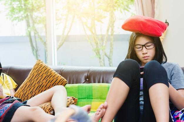 Menina asiática doce que joga o jogo no telefone móvel em casa
