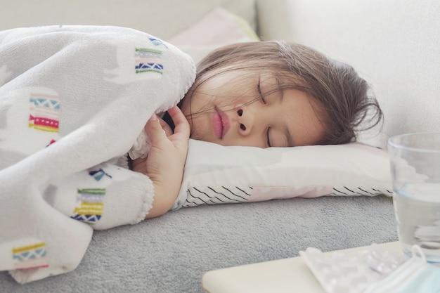 Menina asiática doente deitada no sofá com comprimidos mastigáveis em casa, conceito de cuidados de saúde