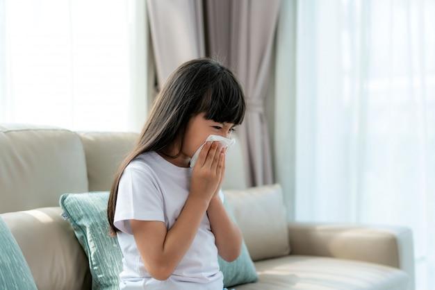 Menina asiática doente e triste com espirros no nariz