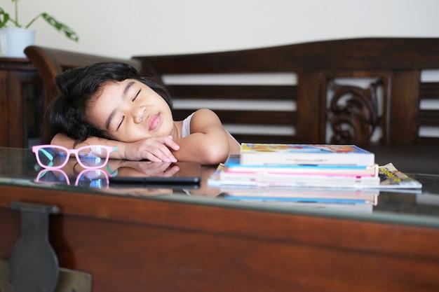 Menina asiática dormindo na mesa durante o estudo dentro de casa
