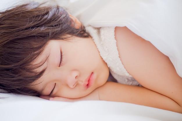 Menina asiática dormir na cama, criança doente, sono de criança