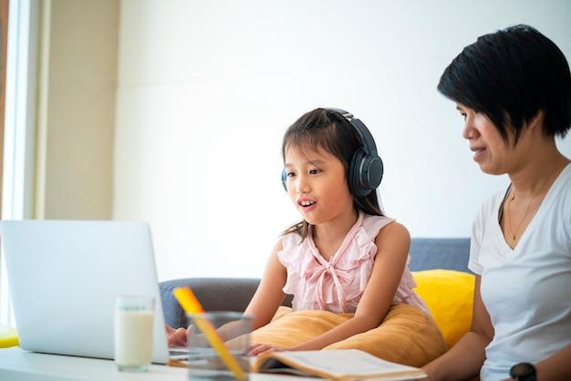 Menina asiática e a mãe dela usando o laptop para estudar online durante o ensino doméstico em casa. ensino doméstico, estudo online, novo normal, aprendizado online, vírus corona ou conceito de tecnologia educacional