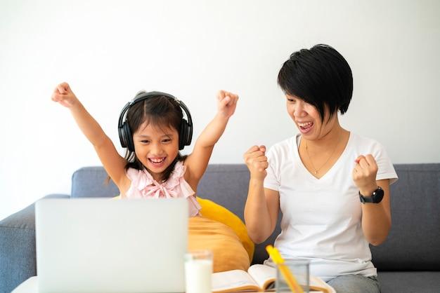 Menina asiática e a mãe dela usando o laptop para estudar online durante o ensino doméstico em casa.