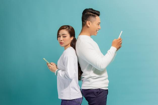 Menina asiática e cara sorridente de costas um para o outro, usando telefones celulares sobre o azul