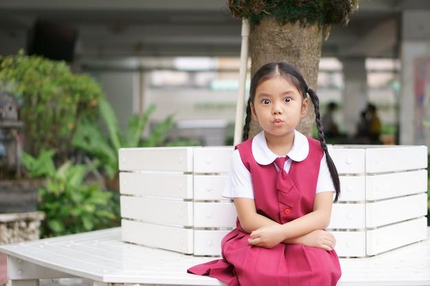 Menina asiática e estudante olho grande com encurtar a boca ou enrugar com feliz alegre e usar uniforme escolar