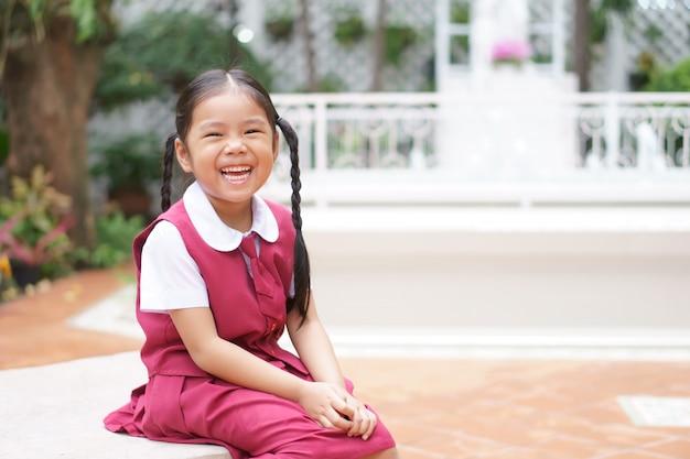 Menina asiática e estudante sorrindo feliz com rir alegre e usar uniforme escolar para a educação