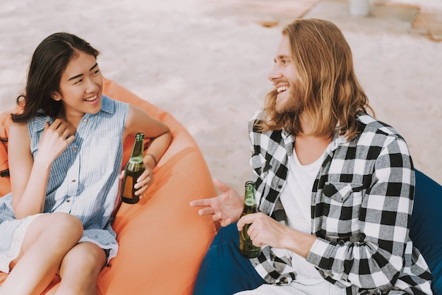 Menina asiática e homem caucasiano na festa de praia