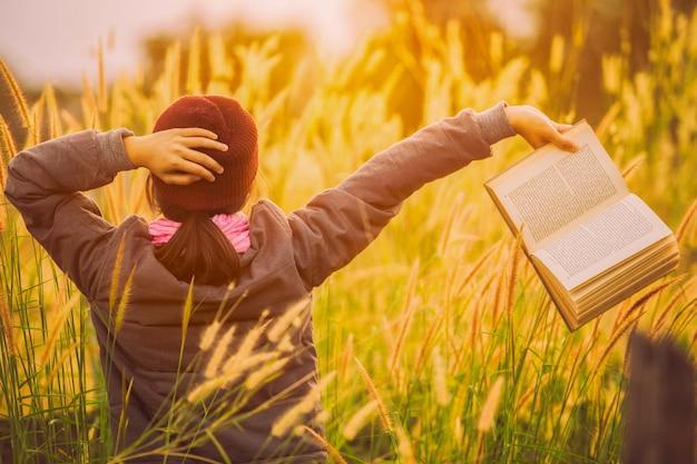 Menina asiática e livro em um inverno do prado.