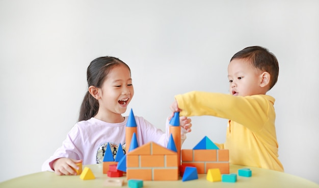 Menina asiática e menino brincando com brinquedos de madeira