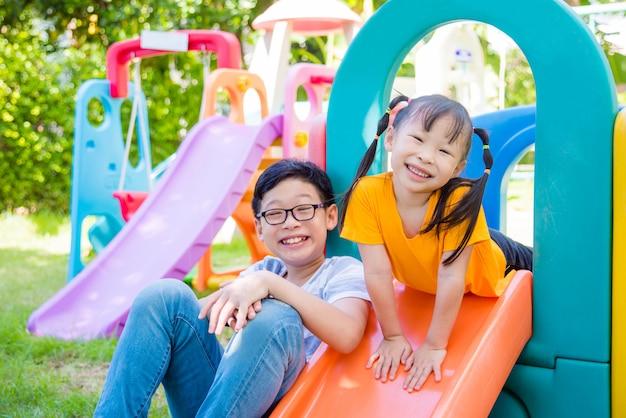 Menina asiática e seu irmão brincando no playground da escola