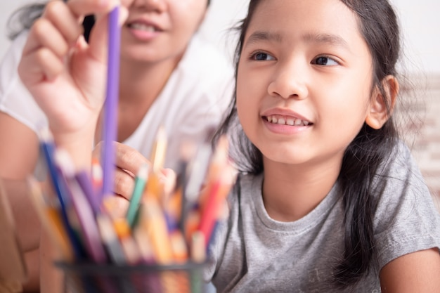 Menina asiática e uma mulher que seleciona uma cor para pintar