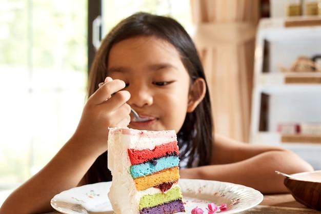 Menina asiática eatting bolo no café.