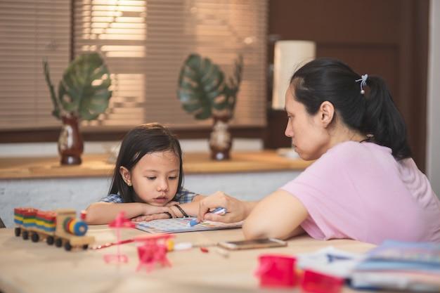 Menina asiática em casa, fazendo lição de casa, estudando e lendo na sala de estar com a mãe em casa. jovem adulta ensinando sua filha a aprender a distância
