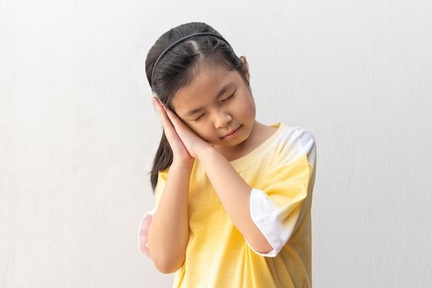 Menina asiática em pé e dormindo isolado na cinza