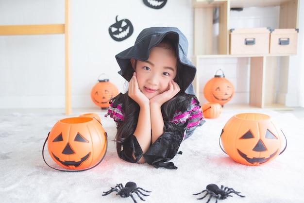 Menina asiática em traje de bruxa deitado no chão
