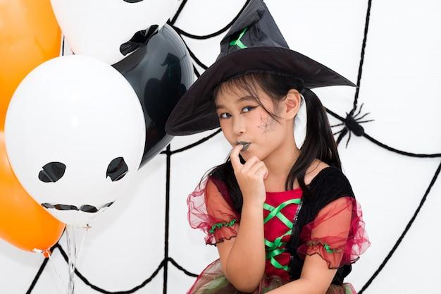 Menina asiática em traje de bruxa