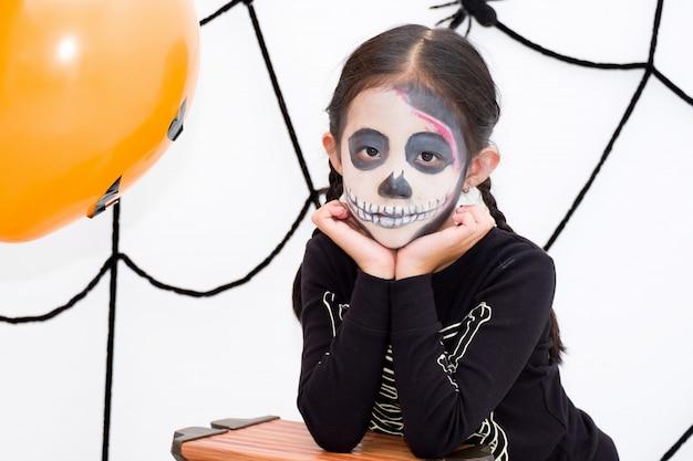 Menina asiática em traje de esqueleto