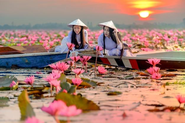 Menina asiática em traje nacional do vietnã, sentado no barco no mar vermelho de lótus em undon thani, tailândia.