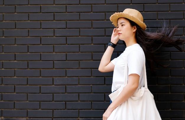 Menina asiática em um fundo escuro da parede