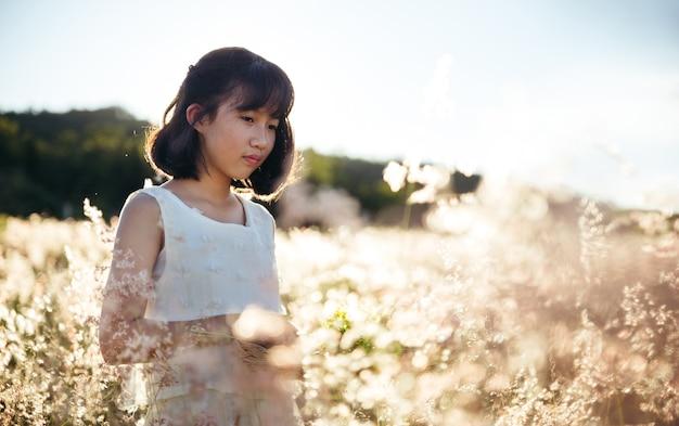 Menina asiática em um vestido branco no campo ao pôr do sol, ao ar livre, curtindo o conceito de natureza.