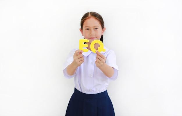 Menina asiática em uniforme escolar, segurando o texto do alfabeto eq (quociente emocional) no rosto, sobre fundo branco. conceito de educação. foco no texto em mãos