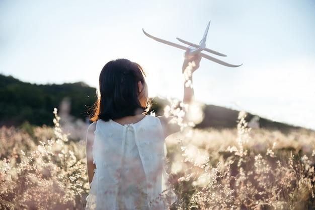 Menina asiática em vestido branco jogando planador em campo ao pôr do sol, ao ar livre, curtindo a natureza e o futuro conceito de sonhar.
