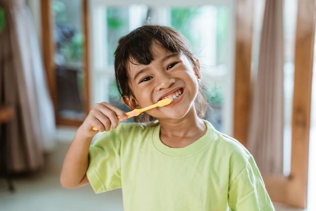 Menina asiática escova os dentes