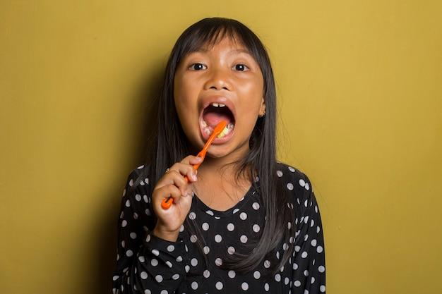 Menina asiática escovando os dentes