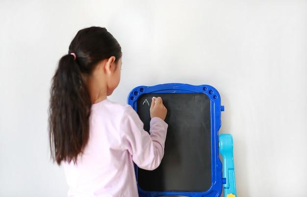 Menina asiática, escrevendo em um quadro negro em branco