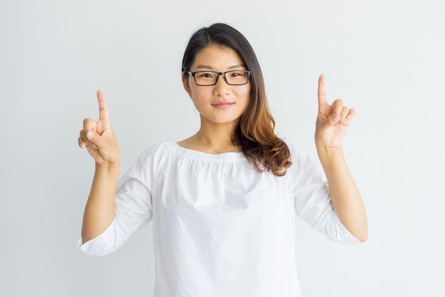 Menina asiática esperta séria com cabelo destacado que aponta acima com dedos.