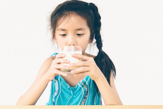 Menina asiática está bebendo um copo de leite sobre fundo branco