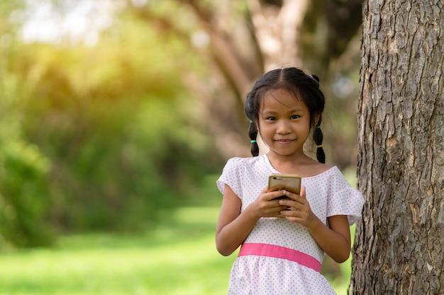 Menina asiática está brincando com um telefone celular no parque.