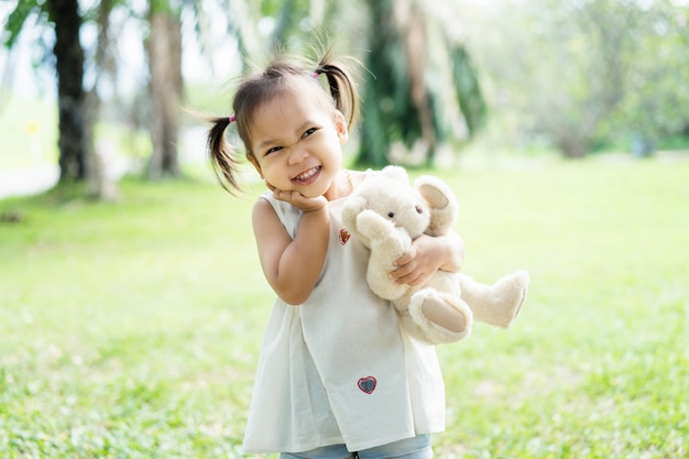 Menina asiática está descansando no parque primavera. criança se divertindo no parque.