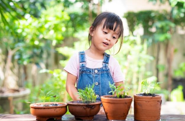 Menina asiática está falando com suas plantas nos potes