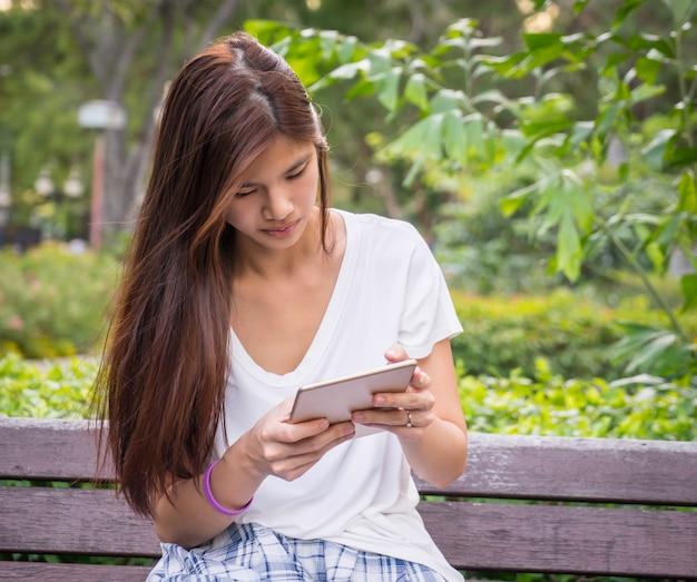 Menina asiática está lendo o livro tablet e