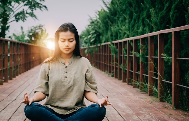Menina asiática está meditando.