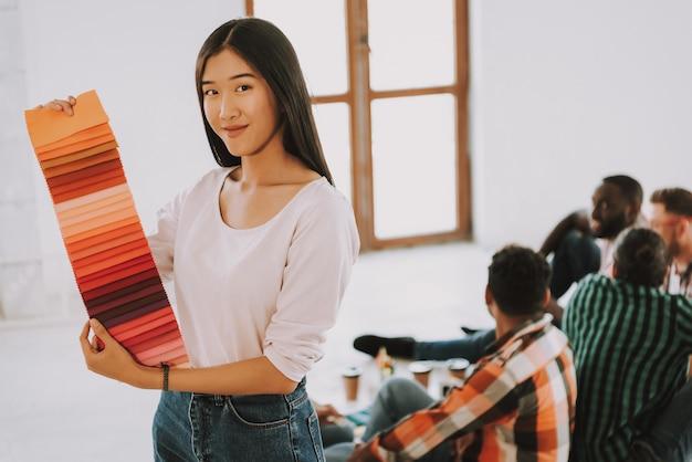 Menina asiática está segurando a paleta de cores e sorrindo