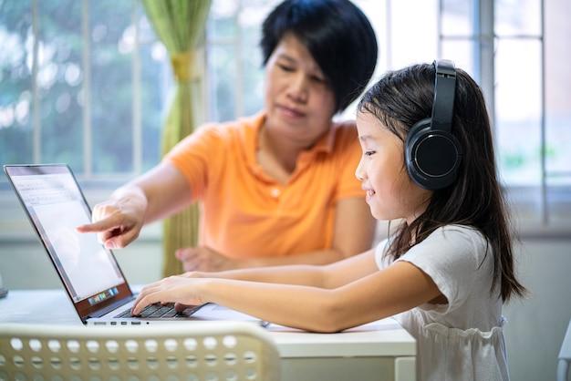 Menina asiática estudando em casa com um laptop e aprendendo online em casa
