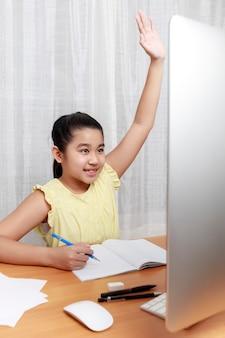 Menina asiática estudando online pela internet, sentada e escrevendo na sala de estar em casa
