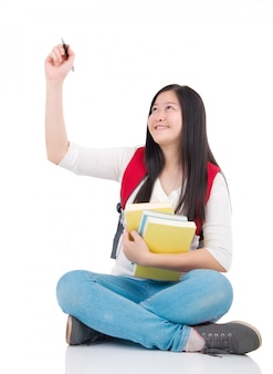 Menina asiática estudante sentado e desenho sobre fundo branco