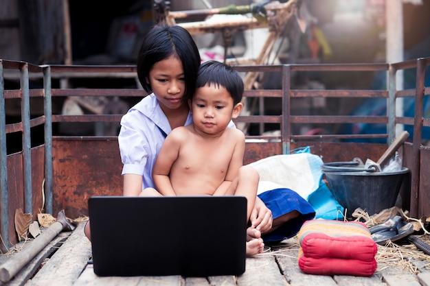 Menina asiática estudante uniforme e seu irmão usando o computador