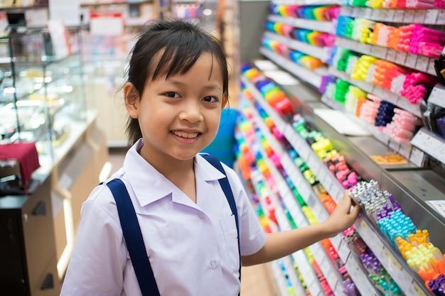 Menina asiática estudante uniforme em papelaria compra canetas e material escolar