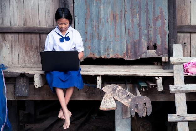 Menina asiática estudante uniforme usando computador notebook