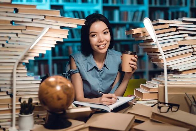 Menina asiática étnica cercada por livros na biblioteca. aluno está escrevendo no caderno.