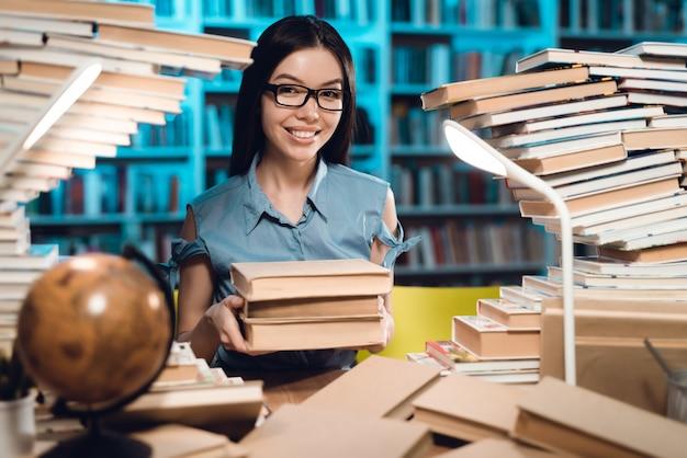 Menina asiática étnica que senta e que guarda livros.