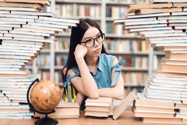 Menina asiática étnica que senta-se na tabela cercada por livros na biblioteca.