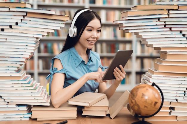 Menina asiática étnica que senta-se na tabela cercada por livros.